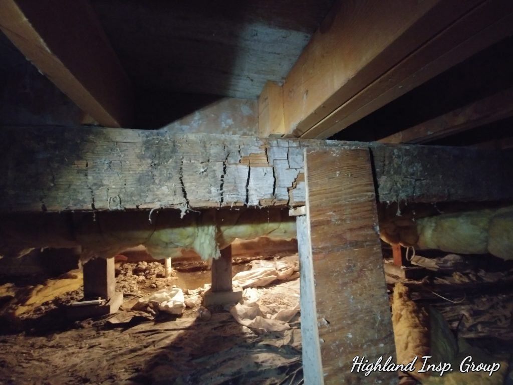 Neglected crawlspace near Missoula has rotted support beam under the home.